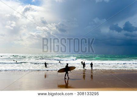 Surfers With Surfboards On The Beach. Rainy  Sky. Algarve, Portugal