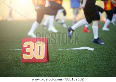 Picture of soccer field with number thirty running football players on blurred background
