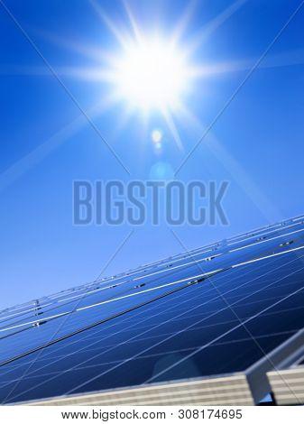 Sun over blue solar panel. Renewable, alternative solar energy, sun-power plant on sky background.