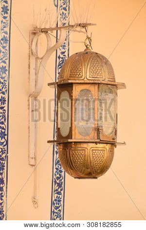 Udaipur, Rajasthan / India - 25 June 2019: Abstract Background Of Gold Vintage Lamp Hanging On Wall