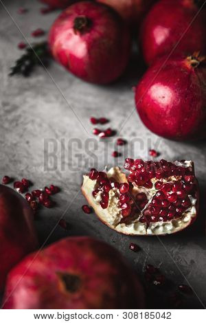Pomegranate Fruit. Ripe And Juicy Pomegranate On Rustic Grey Background With Copy Space For Your Tex