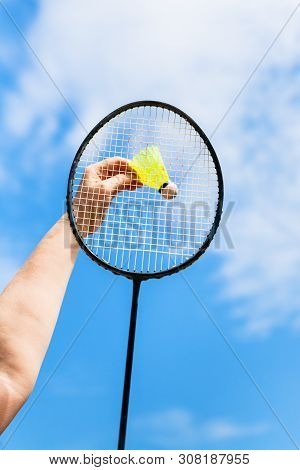 Female Hand Hits Yellow Shuttlecock By Badminton Racquet With Background From Blue Sky With White Cl