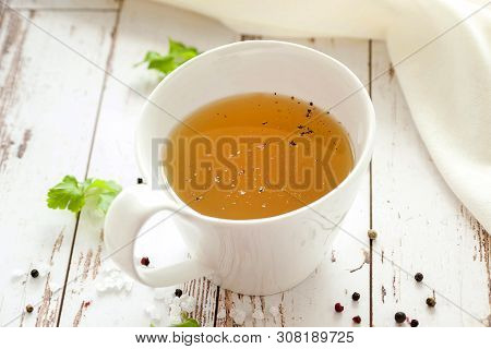 Cooked Hot Bone Broth With Spices And Fresh Herbs. Medical Dietary Broth And Superfood. For Ketogeni
