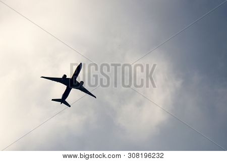 Silhouette Of Airplane Flying In Sky With White Clouds. Commercial Plane During Take Off, Concept Of