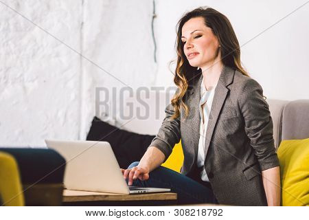 Concentrated At Work. Confident Young Adult Middle-aged Woman In Smart Casual Clothes, Working On A