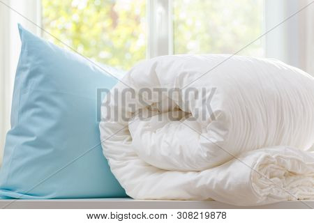 A Rolled Duvet And Pillow Lie On A Dresser Against The Background Of A Blurred Window. Household.