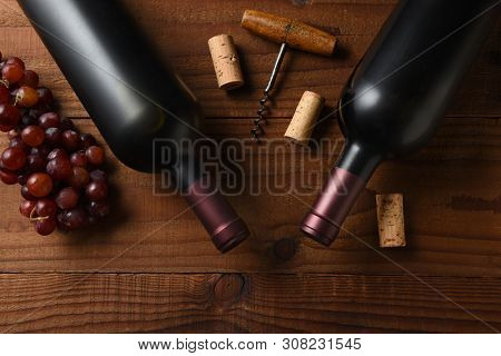 Wine Still Life: Two Cabernet Sauvignon wine bottle short from directly above on a dark wood table with grapes corks and cork screw and copy space.