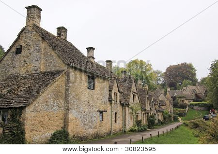 Row of traditional cottages built of golden limestone in Bilbury Village The Cotswalds Gloucestershire England poster