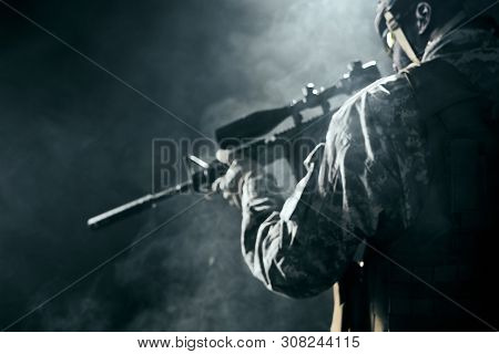 Selective Focus Of Modern Black Gunshot In Hands Of Soldier. Ranker Holding Weapon In Hands And Keep