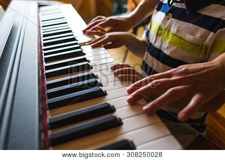 Children's And Women's Hands On The Piano Keys.