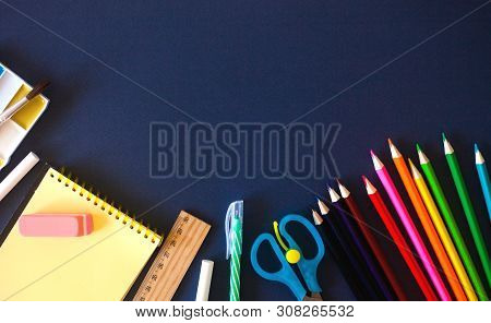 School Supplies On Dark Blue Background. Back To School Concept. Flat Lay, Copy Space.
