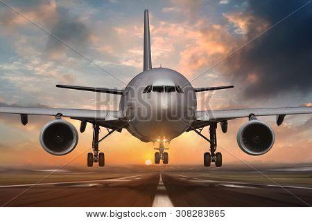 Airplane Landing On Airport Runways During Sunset