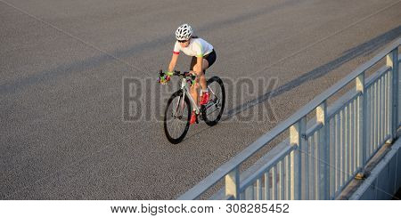 Young Woman Cyclist Riding Road Bicycle on the Bridge in the City at Summer Sunset. Healthy Lifestyle and Urban Sport Concept.