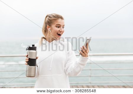 Image of excited blonde woman 20s wearing white hoodie using earpods and cellphone while drinking water from bottle in boardwalk