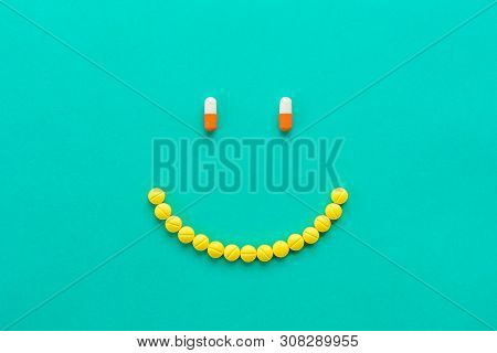 Medical Capsules And Pills Arranged In Happy Smilng Face On Green Background