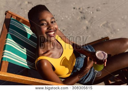 Portrait of African-american woman with cocktail glass relaxing in a beach chair on the beach