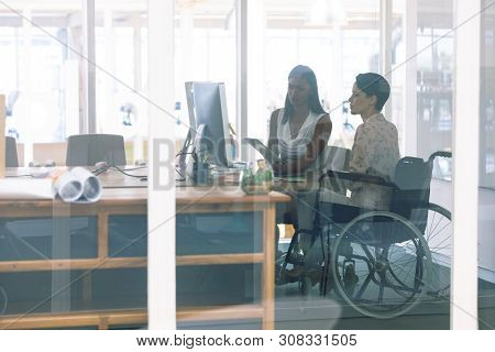 Side view of mixed race female graphic designers working together at desk in a modern office. Disabled mixed-race female designer is sitting in wheelchair.
