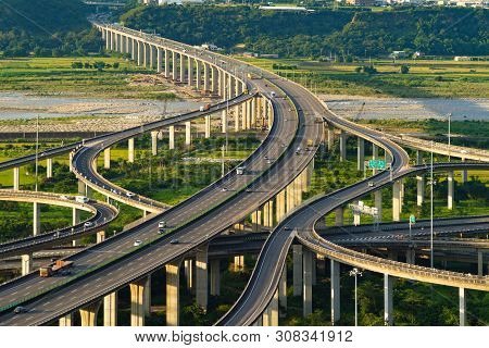 Aerial View Of Cars Driving On Complex Highway Or Freeway With Trees. Bridge Roads Or Streets In Str