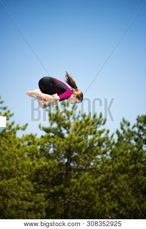 Little Caucasian Female 8 Years Old Girl Jumping In Crouching Position From Diving Platform.