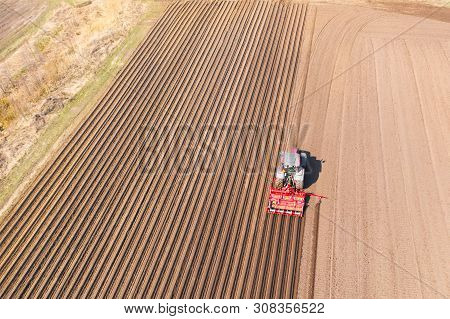 Tractor with disc harrows on farmland, top view. Tractor cuts furrows in a plowed field. Preparing the field for planting vegetables. Agricultural work with a tractor. poster
