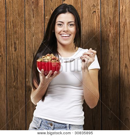 woman holding a delicious red breaksfast bowl against a wooden background