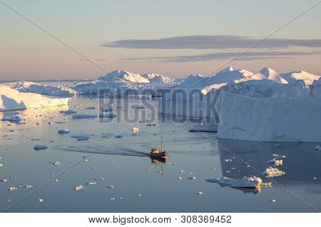 Ilulissat, Greenland - July 7, 2018: A Red Fishing Boat Sailing In Between Icebergs On Ilulissat Ice