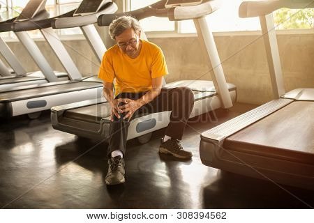 Senior Asian Sport Man Injury Knee Pain  Sitting On Treadmill In Fitness Gym . Aged  Suffering From
