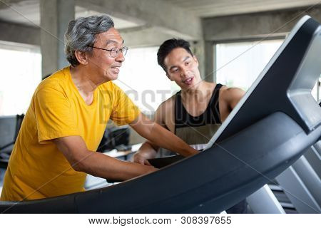 Asian Senior Man Walking Exercise On Treadmill With Personal Trainer Workout In Fitness Gym . Sport
