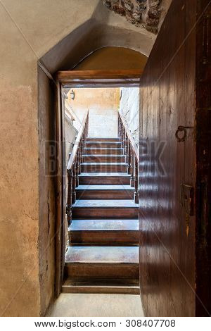 Open Wooden Door Revealing Wooden Old Staircase Going Up With With Reflections Of The Stairs On The