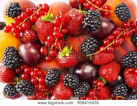 Mix Berries And Fruits On White Background. Ripe Blackberries, Strawberries, Red Currants, Plums And