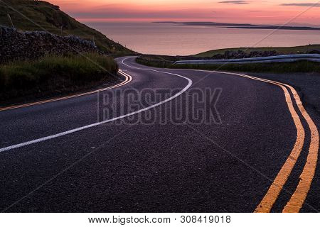 Looking Down A Sweeping Road Near The Cliffs Of Moher To  Beautiful Pink Sky Sunset Over The Island
