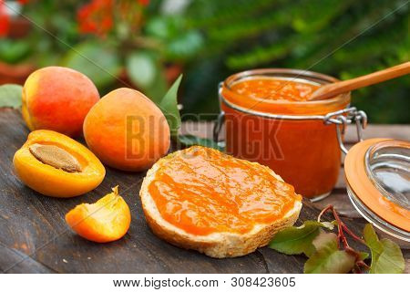 Apricot Jam In A Glass Jar And Fresh Apricots On Wooden Background. Bread Slice With Apricot Marmala