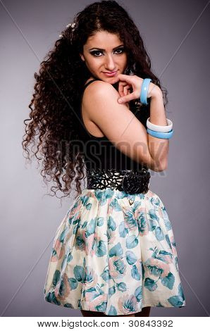 Beautiful young woman in dress on dark background.