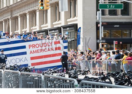 2018 JUNE 24 NEW YORK: NYC Pride March participants ride on the top deck of the SKYY Vodka Proudly American float on the 5th Ave parade route.