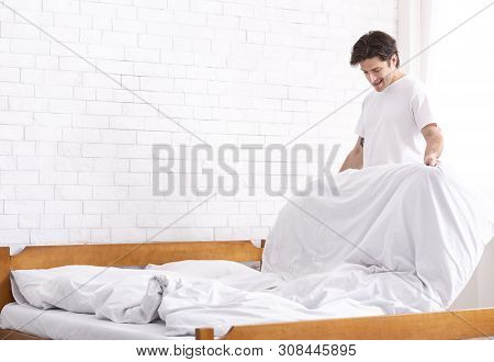 Living alone. Millennial guy making bed in morning, domestic chores concept, empty space poster