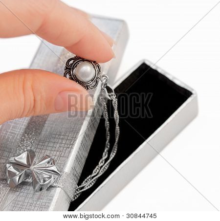 Closeup Of Hand Holding A Necklace With One Pearl