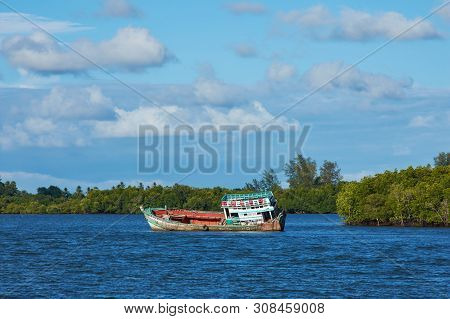 A Boat In A River With Mangrove Background And Bright Sky.
