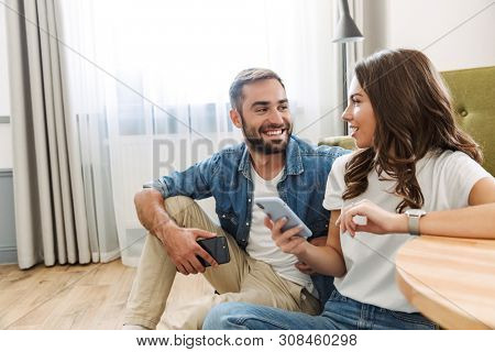 Beautiful young couple in love at home, sitting at the living room, using mobile phones