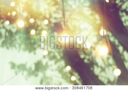 Blurred Bokeh Light On Sunset With Yellow String Lights Decor In Tree