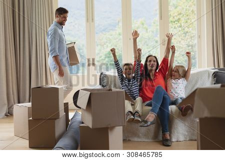 Front view of happy Caucasian family having fun while moving houses in living room at home