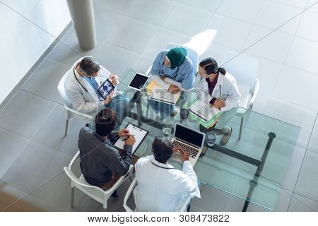 High angle view of diverse medical team discussing x-ray report over digital tablet at table in hospital. Coffee cup, medical folders, clipboard, digital tablet and laptop are on the table.