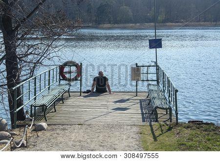 Man Sitting Dock Lake Spring Sunshine Stockholm, Sweden