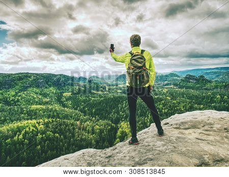 Man Tourist Hiking Mountain Trail, Takes Picture By Phone. Hiker Walking On Rocky Hill, Wearing Back
