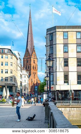 Hamburg, Germany - July 23, 2017: A Young Saxophonist In The Old Town With The St. Peter Church And