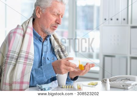 Portrait Of Sad Sick Senior Man With Medicine