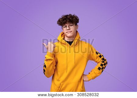 Positive youngster in yellow hoodie and round spectacles looking at camera and pointing aside with thumb while standing against bright violet background poster