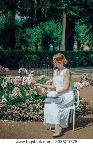 Young Beautiful Woman In White Dress In The Green Garden With Flowers Close Up In Summertime