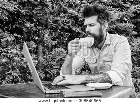 Balancing Between Work And Pleasure. Hipster Drinking Tea And Using Computer Work Station Outdoor. B