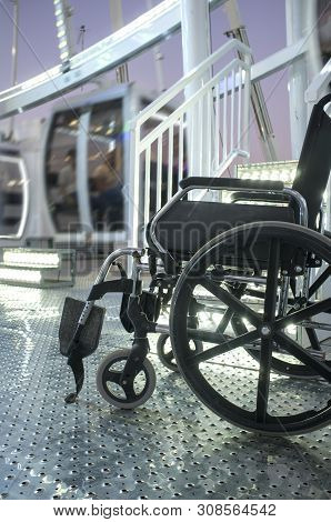 Wheelchair Close To The Hall Of Ferris Wheel At Fairground. Fairground And And Disability Concept