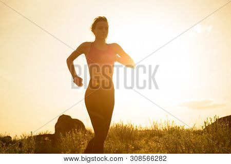 Young Beautiful Woman Running on the Mountain Trail at Hot Summer Sunset. Sport and Active Lifestyle Concept.